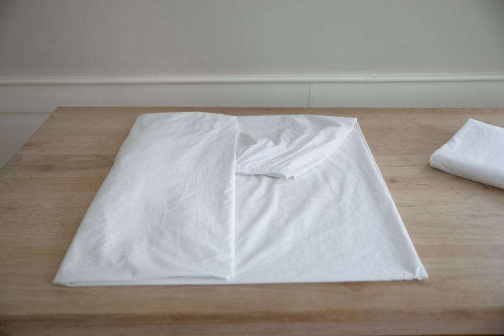 Using a neatly folded flat sheet as a size guide, fold the now-square fitted sheet lengthwise into thirds or quarters.