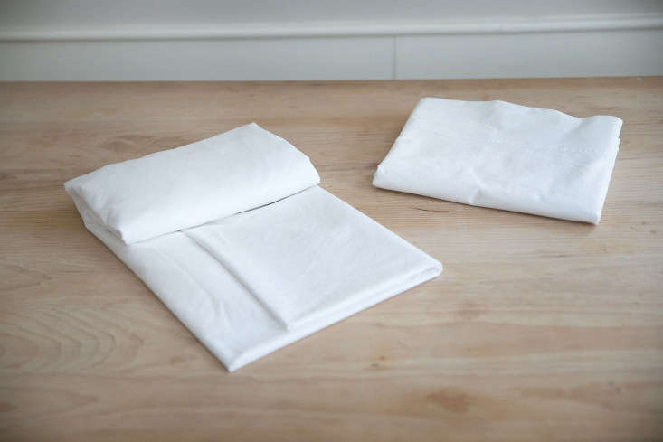 Fold the sheet neatly along the length, perhaps using a folded flat sheet as a guide so that they match sizewise.