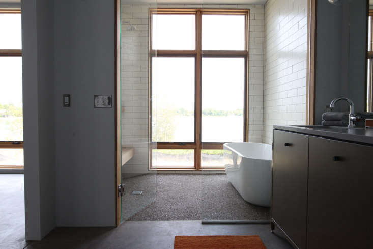 a bathroom with a spacious wet room with exposed and heated aggregate cement fl 19