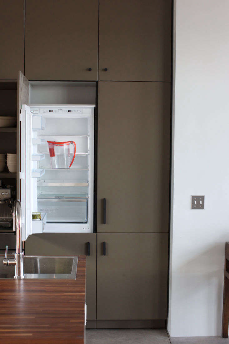 a bosch \24 inch refrigerator is hidden in a system of cabinets with a custom p 11