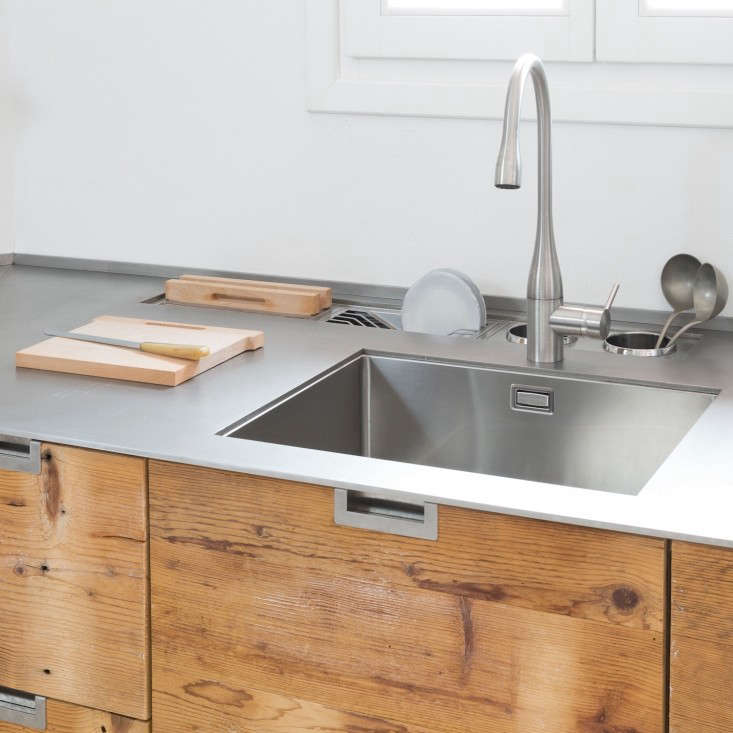 Behind the sink is a stainless steel drying rack, slotted storage for cutting boards, and two caddies for kitchen utensils.