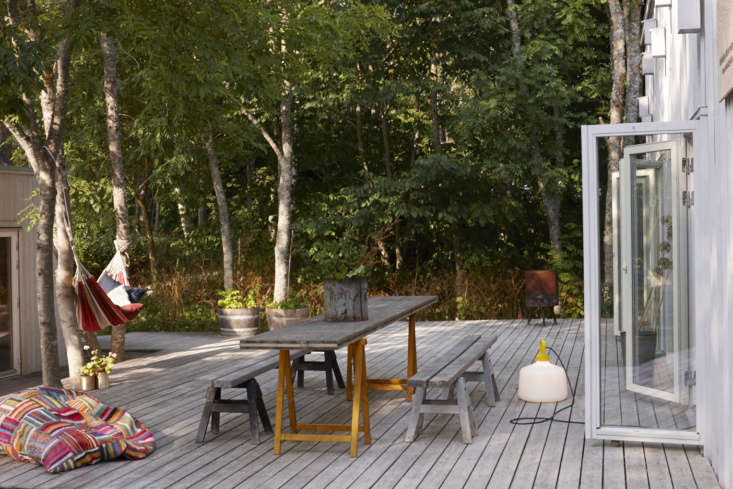 A holiday house in the Swedish forest is possible when working with Leva to create a custom set up. Seen here, two buildings face each other with a deck in between.