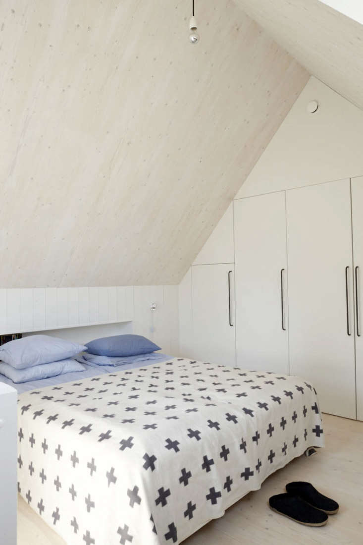 The loft bedroom is designed with beds that partially fit into wall nooks. The closet storage shown here is designed with towel-bar-like pulls, similar to the kitchen hardware. On the bed is a Pia Wallen Cross Blanket and at the foot of the bed is a pair of Glerups felt slippers.