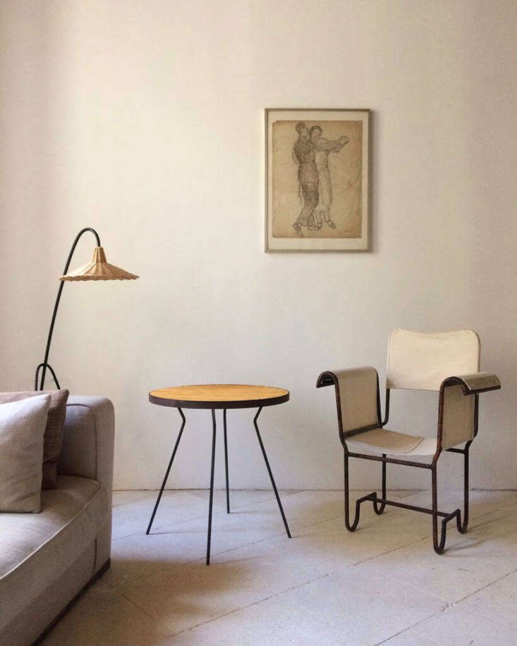 """A Rattan Marquetry and Black Metal Side Table, price on request,and the """"Edith"""" Lamp, €459, an iron tripod with a wicker shade that comes in five styles. The armchair is a vintage canvas and metal design."""