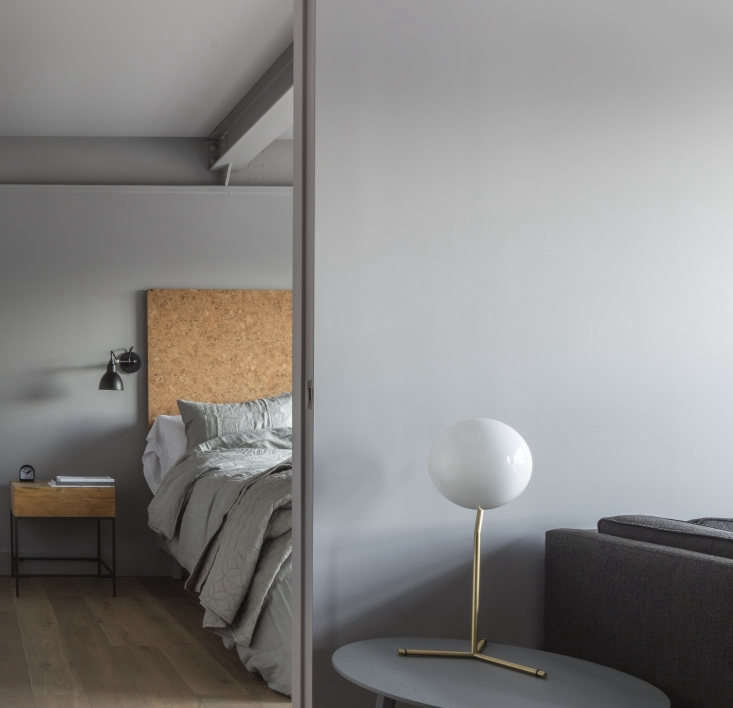 A sliding door divides the bedroom from the living area in this one-bedroom setup. The beds have custom cork headboards and metal and wood side tables. The bedside sconces are the classic Lampe Gras Model 304.