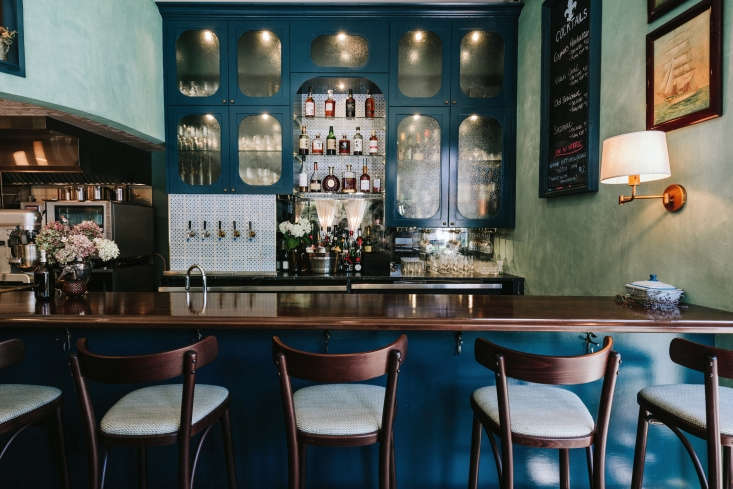 in the next room, a small bar is to the right. the pebbled glass cabinets are a 19