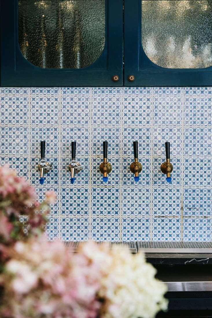 behind a row of brass taps, a blue and white backsplash in tiles by the winches 20