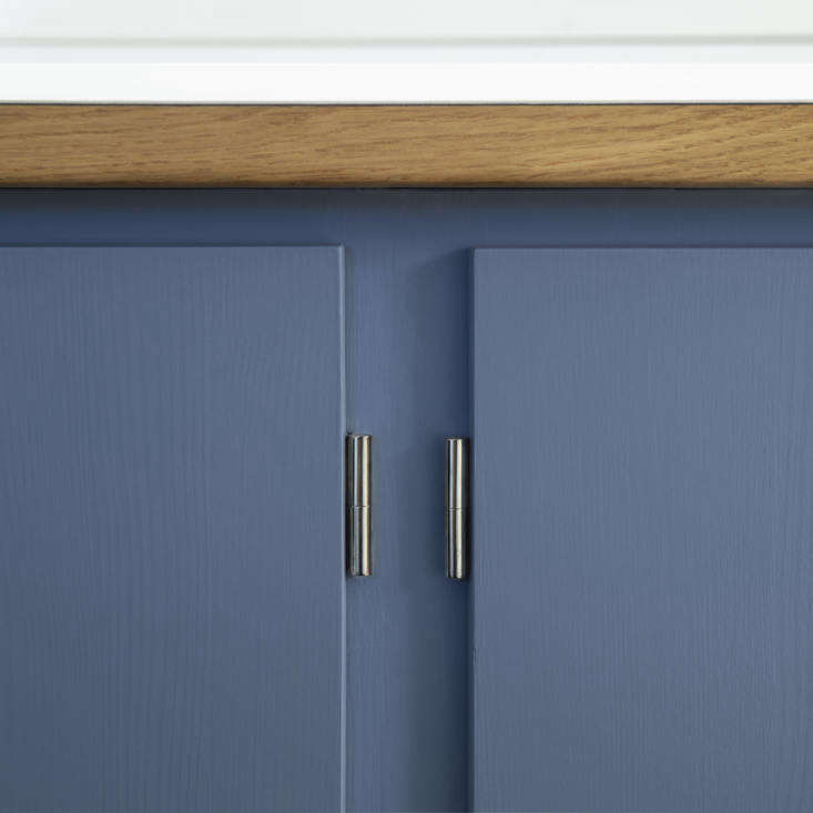 """Hardware is """"old-fashioned chrome that cannot be worn out,"""" as seen here on the hinges. The simple drawer pulls are the same finish. The cabinets are hand painted."""
