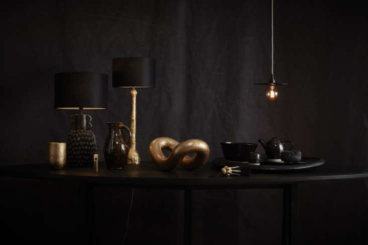 The Large Guardian Table Lamp in Black and Figurative Stem Table Lamp in Gold arranged with other objects from the New Craftsmen.
