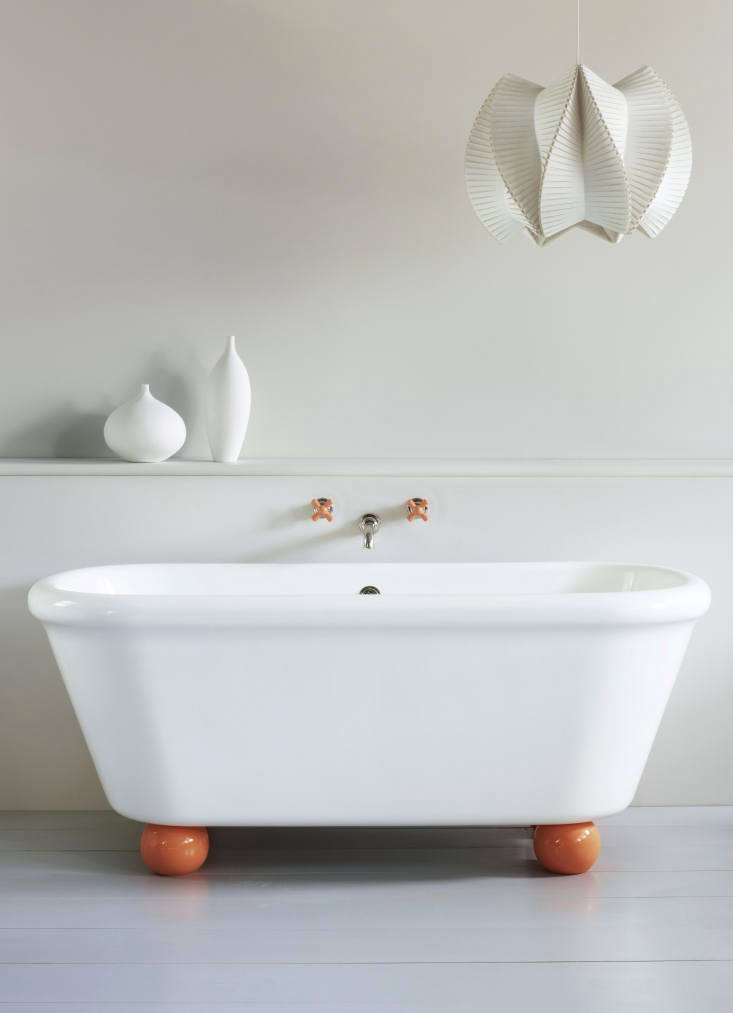 The Rockwell Bath with Feet, shown with Squash Orange-colored feet, is a reproduction of an antique bath and is manufactured in England from Vitrite, a stone and mineral composite that replicates the feel of the original bath; £4,500.