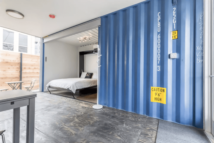 two bright blue shipping containers were turned into a 500 square foot flat in  14