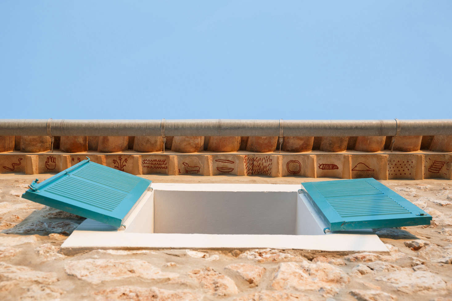 In another nod to Mallorcan tradition, the architects hired artist Luis Urculo to paint small rust-colored symbols beneath the roof tiles—a play on the medieval tradition of teules pintades,said to protect the inhabitants of the house. Of the bright shutters, the architects say, &#8