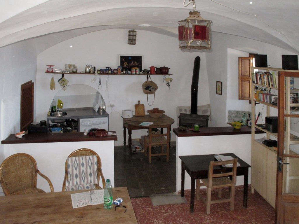 The kitchen and dining room were dark and cluttered, with a half wall that divided the space.