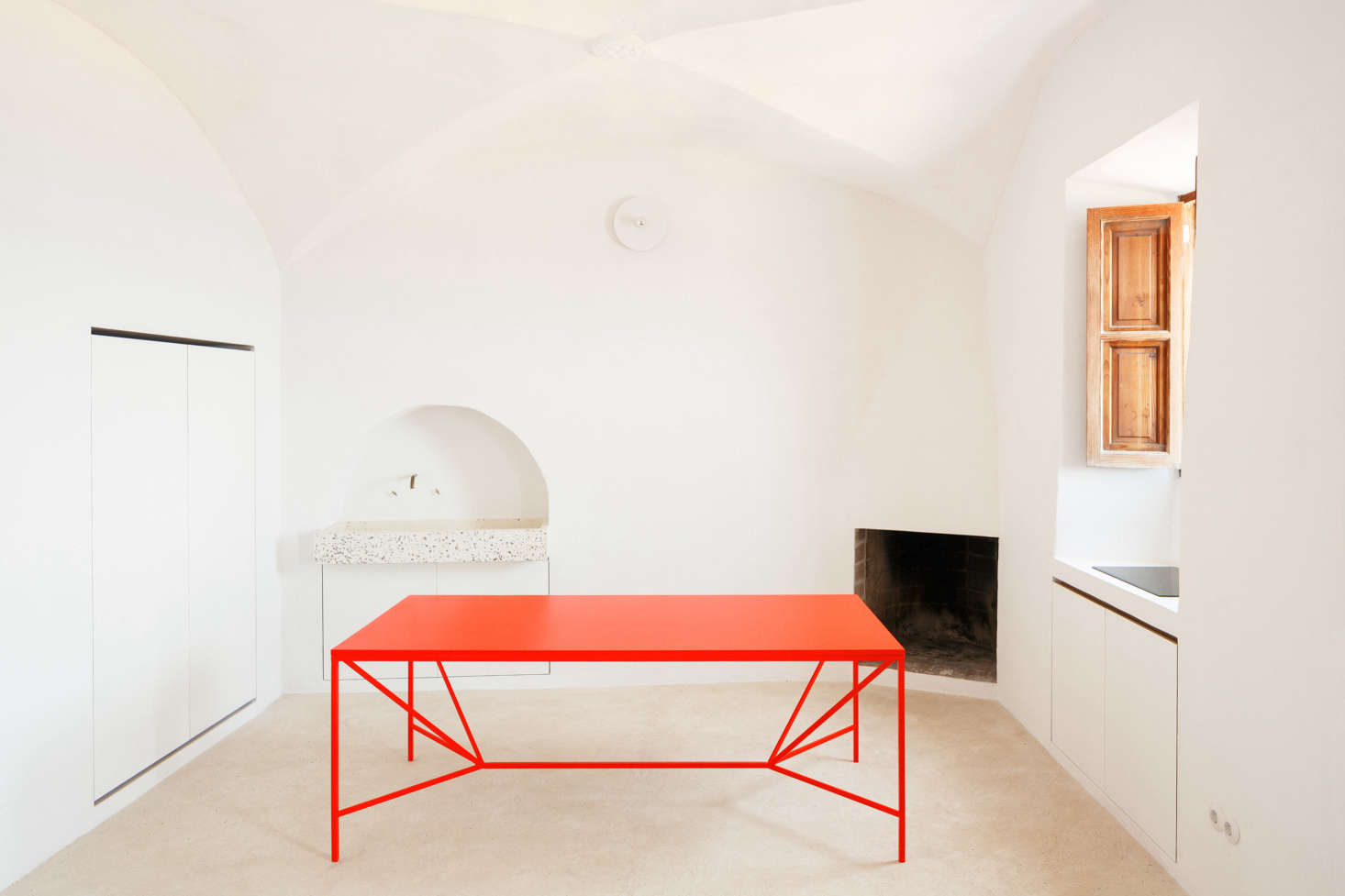 In the streamlined kitchen, nearly everything is concealed within the walls and windowsills. In one corner, the architects uncovered the original fireplace.