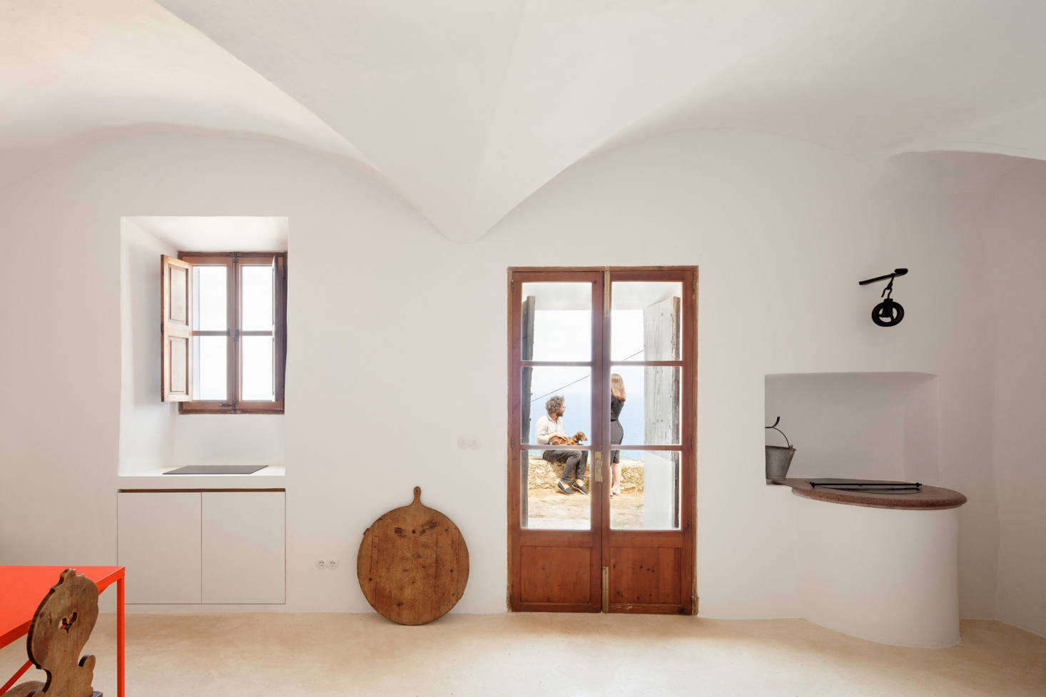 A view toward the front of the house, with the front door, and the cooktop at left. On the right, a circular counter is a well for collecting rainwater, the last vestige of the house&#8