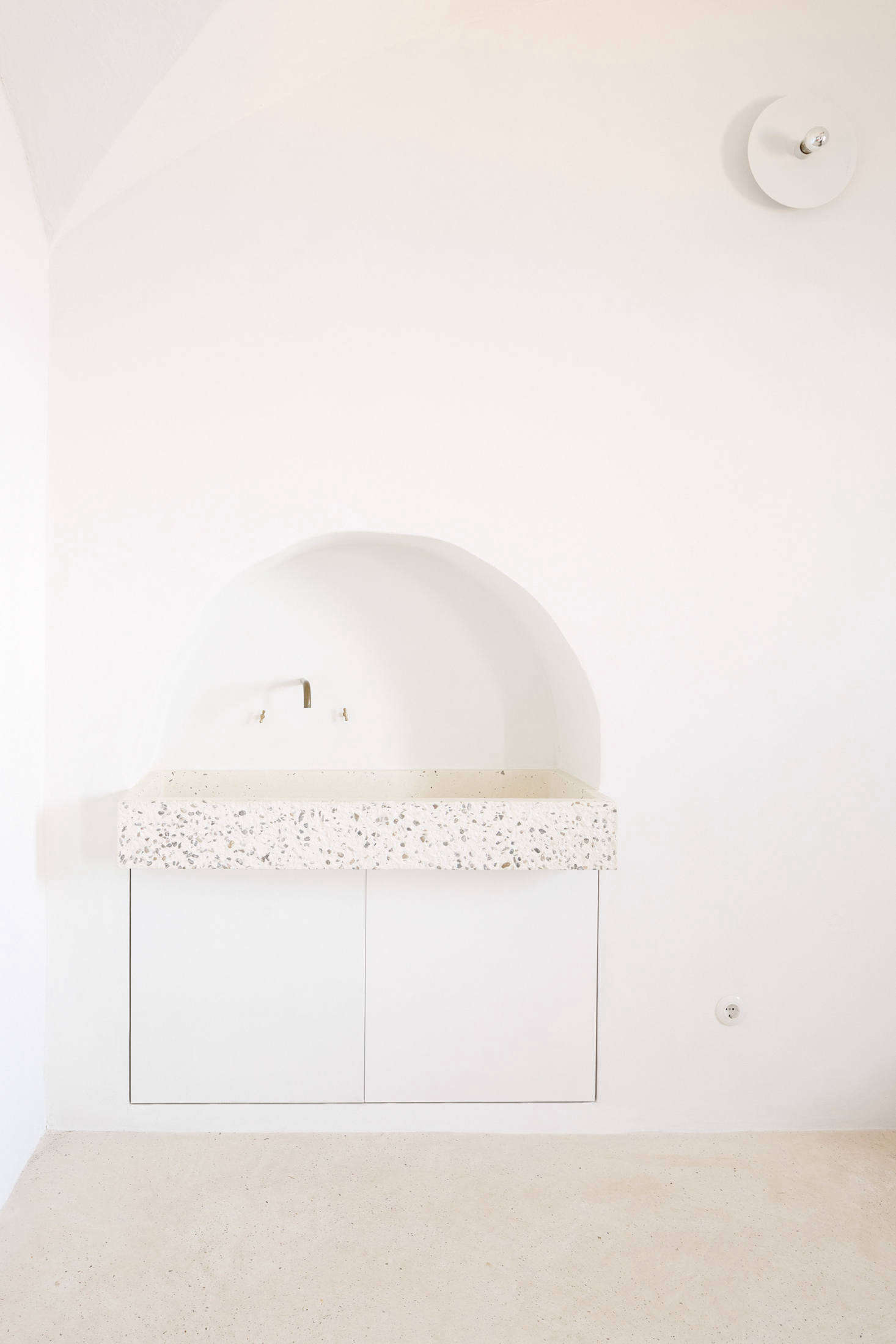 Palencia and Colón preserved a small archway in the kitchen and installed a custom tinted-concrete sink by local company Huguet, a reference to Mallorcan stone sinks. Two cabinets underneath store cleaning products and house the waste bin. Of the subtle white light overhead, the architects say: &#8