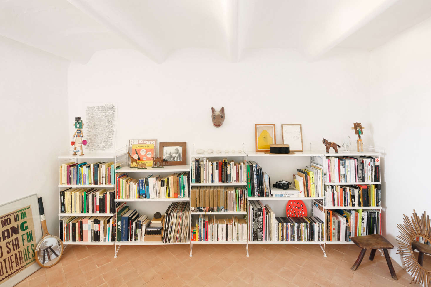 The library has the most lived-in look, with books and finds stashed on low white shelves. Palencia and Colón replaced the existing colored cement tiles with handmade terracotta square tiles &#8