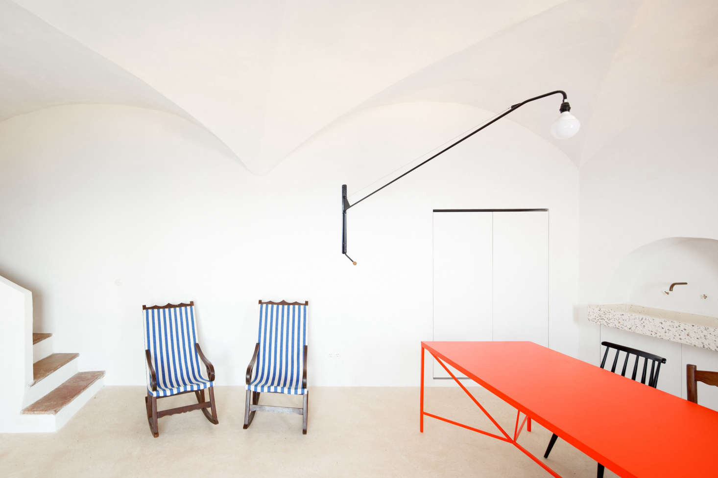 The wooden front doors open into the high-ceilinged main room. Palencia and Colón painted the walls in matte white mineral paint from the German brand Keim, then repaired the vaulted ceilings and painted them &#8