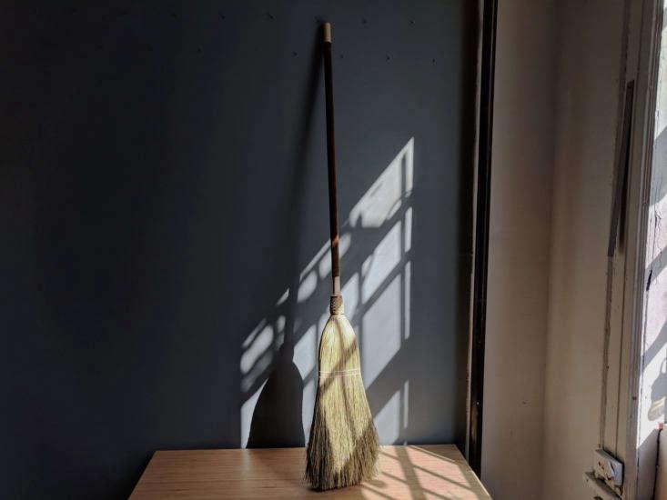 A custom broom has an olive green velvet cover.