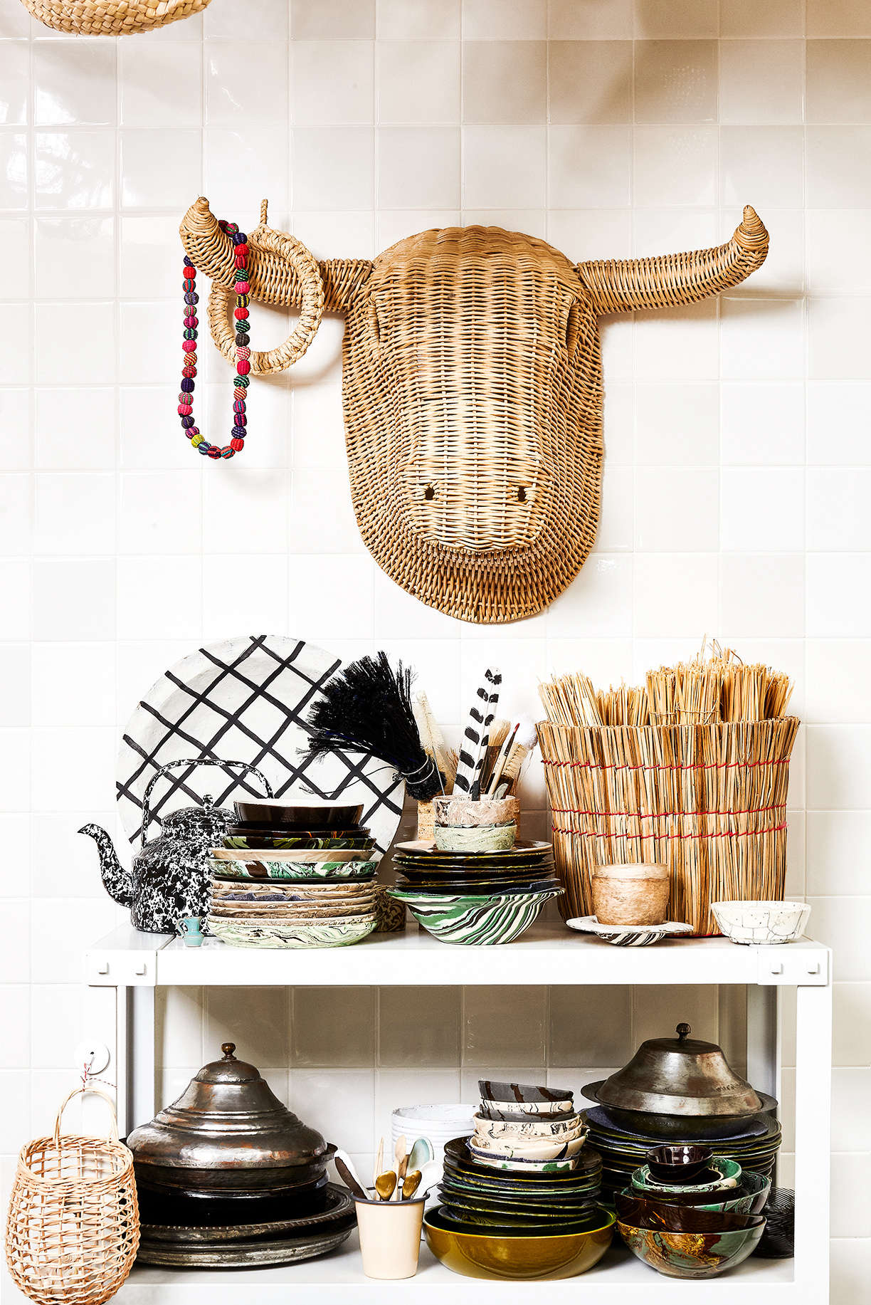 David displays his finds on a freestanding metal shelf. On the top level, a basket from Japan holds a set of rolled up wicker placemats, the spatter teapot is from Merci in Paris, and a paper feather byBrussels-based artist Isabelle de Borchgrave adds a jaunty note. The stacks of bowls are by French ceramicist Sylvie Saint-Andre Perrin(available from John Derian in NYC). On the lower shelf, the metal pieces are from Turkey, and the Shaker onion basket is from the Cooper Hewitt shop. David mounted awicker bull&#8