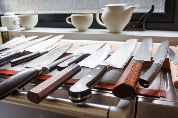 Tools at the ready: A dozen knives are perched on a magnetic knife rack that rests on top of the toaster oven.