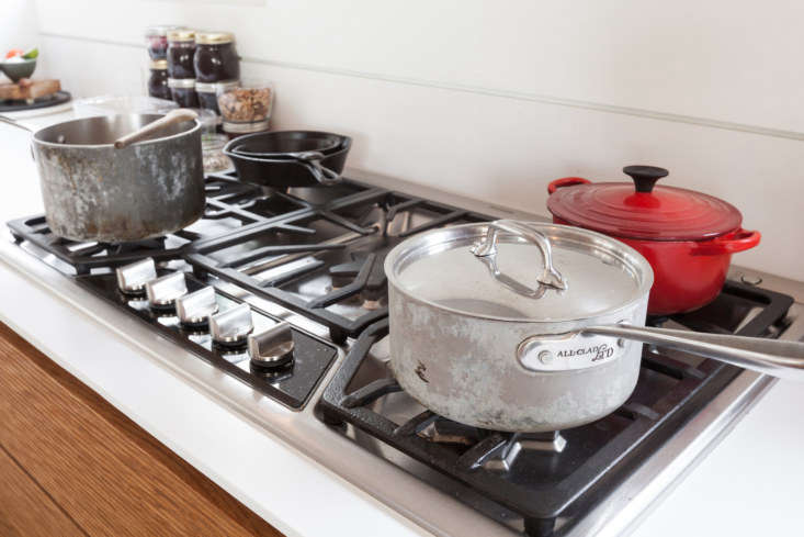 On the five-burner gas range: a pair of well-seasoned cast-iron pans, a red Dutch oven from Le Creuset, and an All-Clad LTD Saucepan.