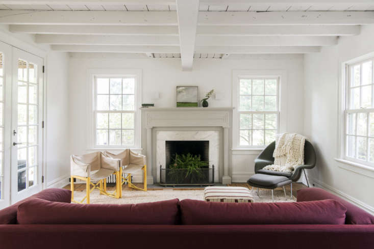 Elizabeth removed built-in shelving in the living room and added French doors to access the screened porch and the pool and yard beyond. Walls (and some floors) are painted inCloud White from Benjamin Moore. Thesofa is Muuto&#8