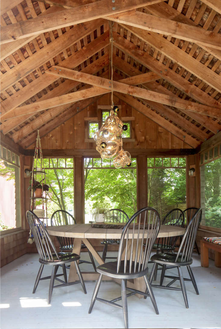 AKnotty Bubbles chandelier by Lindsey Adelman hangs above the round dining table in the screened porch.