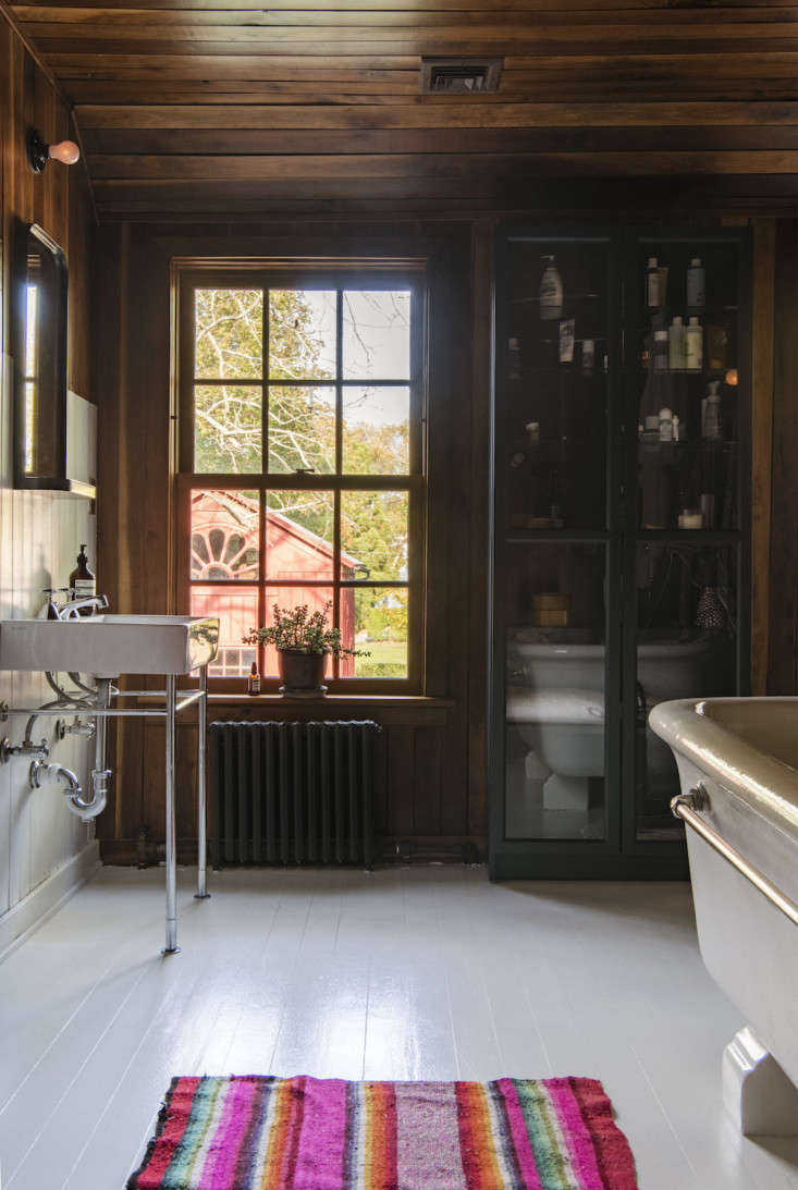 A dark blue glass-fronted cabinet was part of an Ikea limited run. The bath rug echoes the colors in Elizabeth&#8