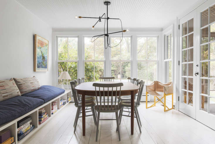 In the dining room, the architect added a wall-to-wall built-in bench with denim cushions and storage cubbies for board games. The chandelier above the dining table is the three-armedIndustrial Chandelier from Workstead.