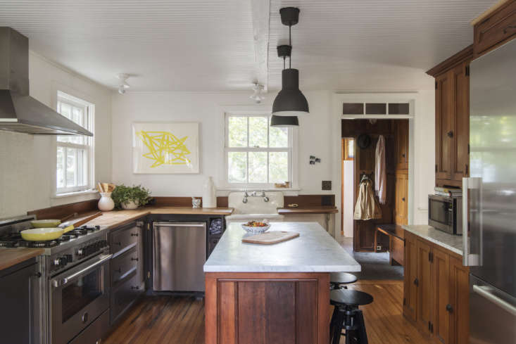 The kitchen cabinets are oak, salvaged from a defunct pharmacy.The counter stools areDalfred from Ikea.