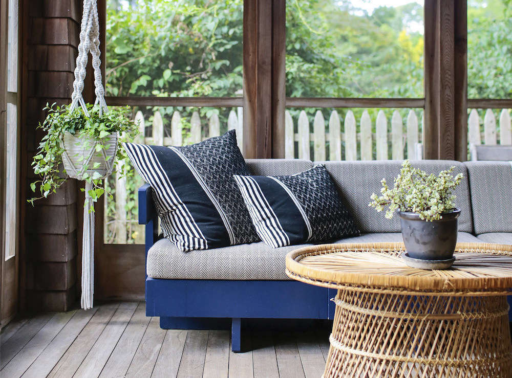 Elizabeth bought the sun porch sofa at auction and had it painted blue and reupholstered. The macramé plant holder is from CB