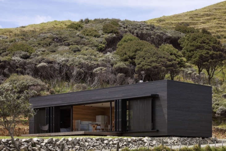 the cottage is clad in rough sawn cedar with a black stained finish. 9