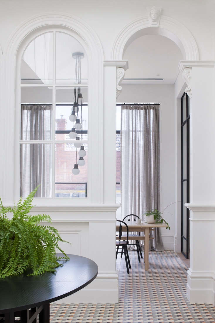 The designers retained the layout of the grand Victorian entryway, adding coral and blue geometric tile throughout the front room, paired with a black Cassina dining table. A new skylight allows natural light to pour in.
