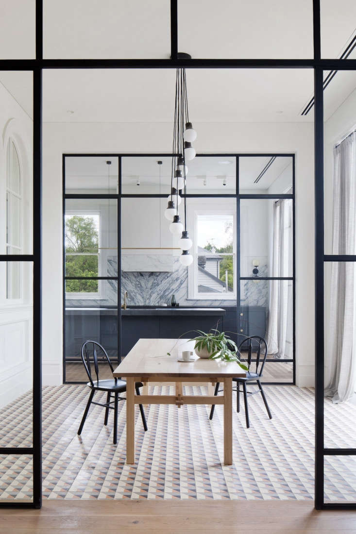 Steel framed interior walls allow natural light to filter through the rooms. In the dining room, a collection of Mass Lights by Norm Architects hangs above a Nikari dining table.