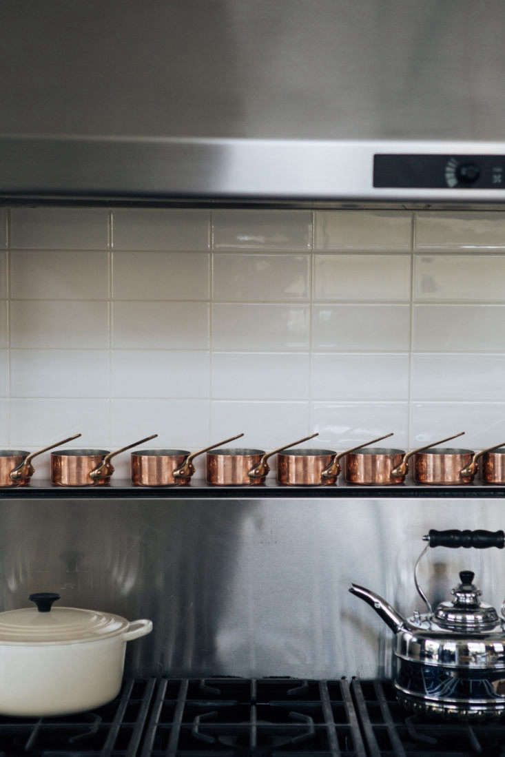 A row of small copper saucepans above the range. Photograph by Laure Joliet from Joan McNamara's Industrial Chic Loft in LA.