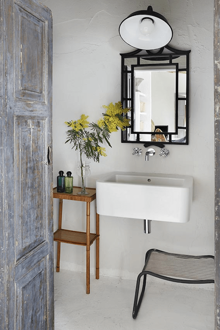 Spanish Eclectic An Airy Stable Turned Guest House on the Mediterranean Coast The bathroom is lit by a black wall light, similar to the one over the kitchen.