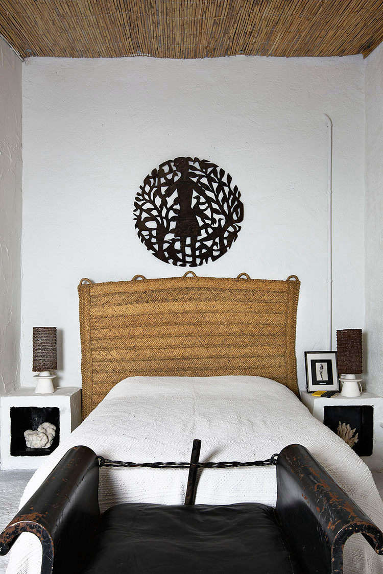 In another bedroom, sculptural built-in nightstands with black-painted niches flank the bed. The rattan headboard is Castella&#8