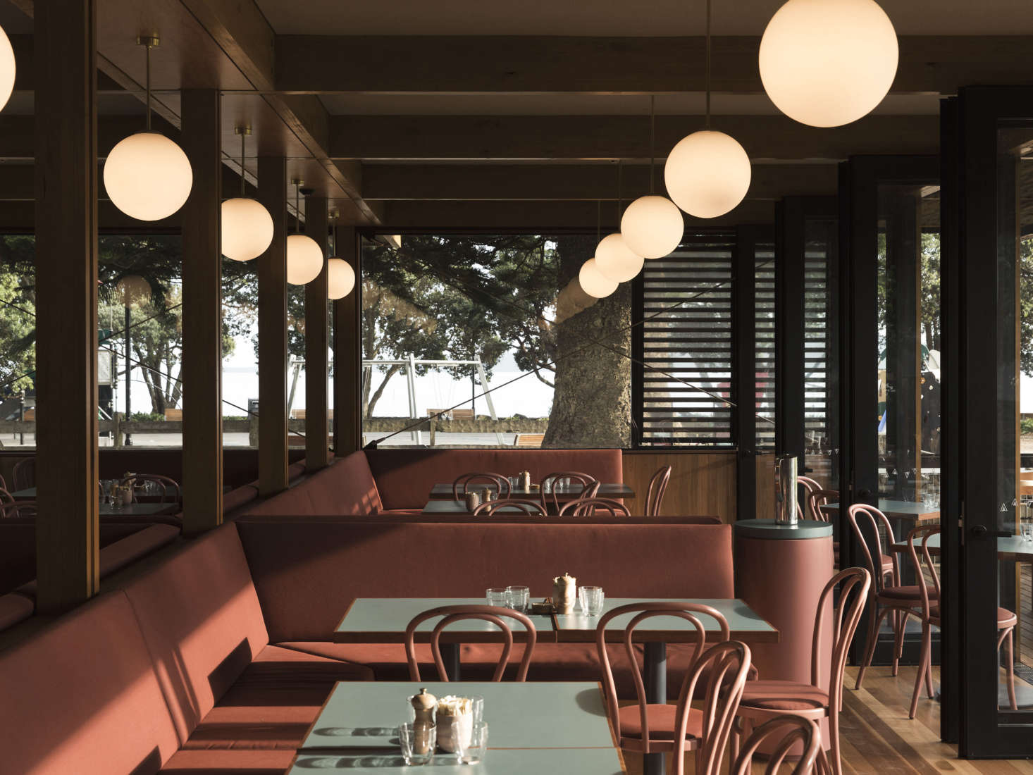 Inside, Lockhart opted for durable surfaces (Mission Bay is Auckland's busiest beach) like painted wood, powder-coated steel, laminate, and Sunbrella fabric. The banquettes are upholstered inTresco Brick Sunbrella Fabric.