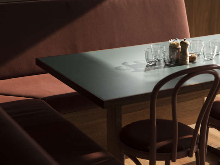 The table tops are made of Spotted Gum laminate tops in Teal from Laminex. Lockhart powder-coated the bases in Dulux Denim Blue. On each table are Duralex Gigogne Tumblers and Peugeot 5-Inch Pepper Mills.