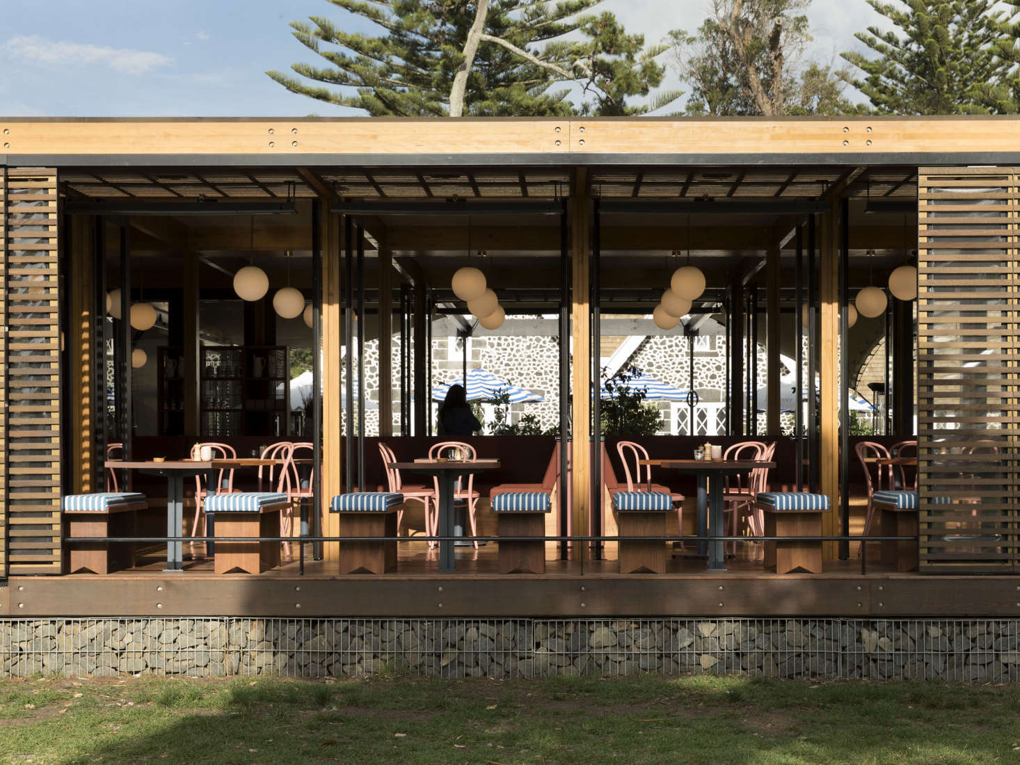 The restaurant addition is designed with cedar slats, blackened steel, and a gabion wall foundation. See the restaurant courtyard and surrounding landscape design by Lockhart&#8