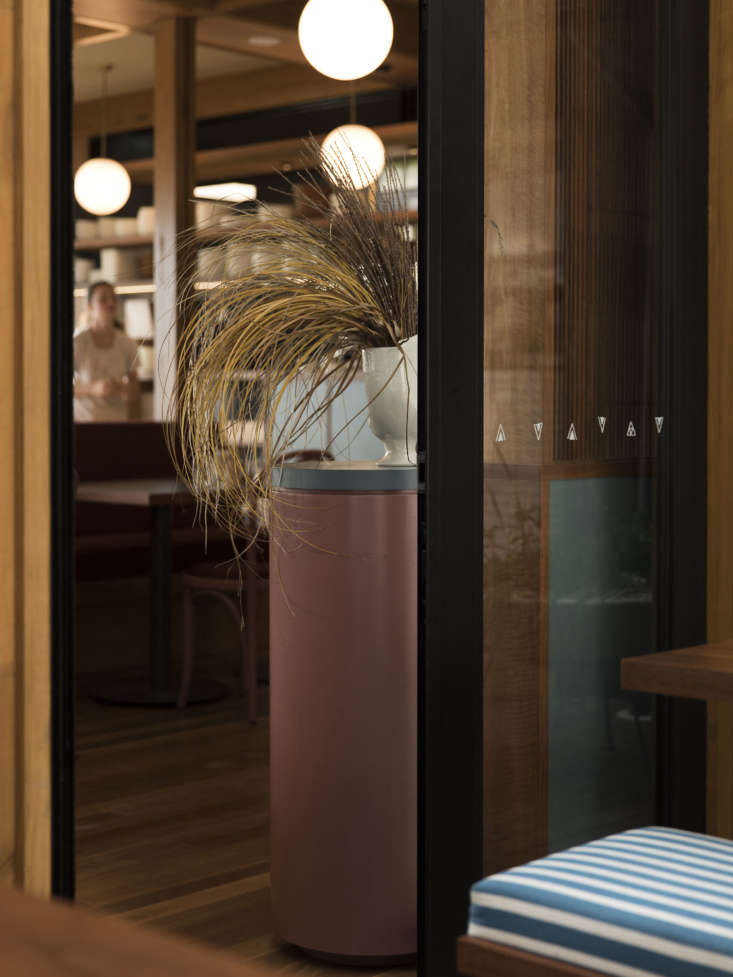 Pillars throughout the restaurant are lacquered in Everyday Needs Clay paint with laminate tops to match the dining tables. The vintage vase seen here was sourced from Babelogue in Auckland and the dried arrangement is by Muck Floral.