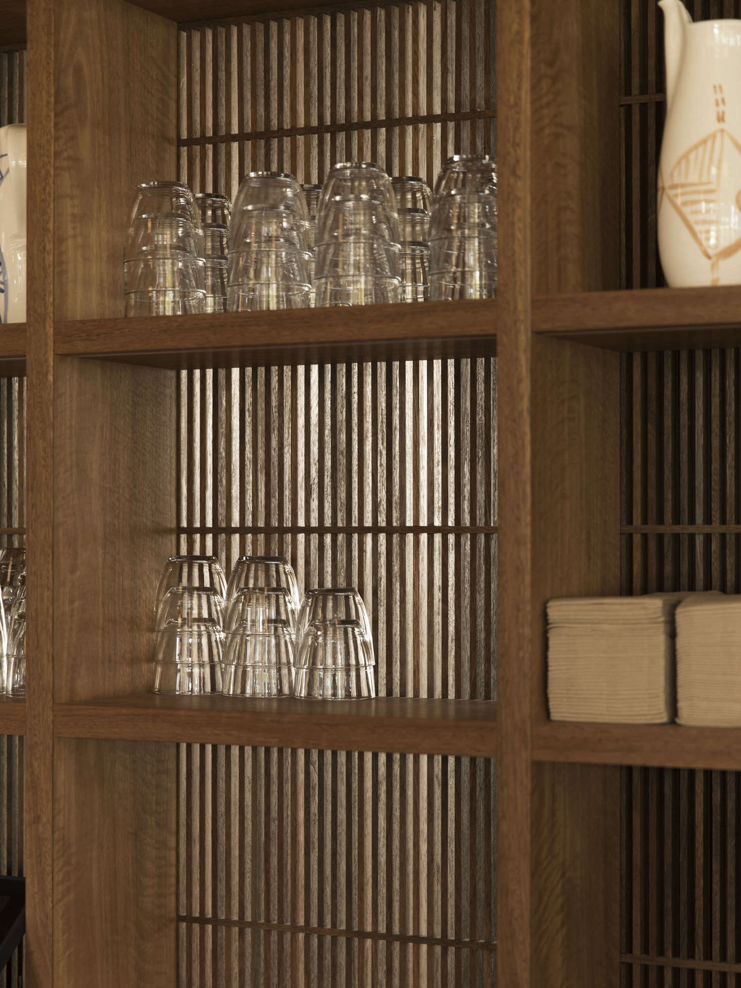 The slatted back of the custom cabinets lets in light and mimics the building's facade.