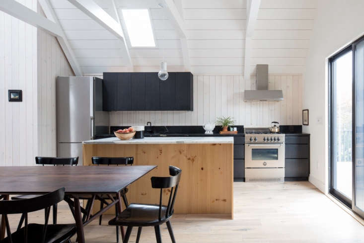 Though the kitchen is compact, it has a full suite of appliances, including a four-burner Bertazzoni range and a Bosch refrigerator (see  Easy Pieces: Best Skinny Refrigerators). The cabinets are pine wood, stained the same black color as the exterior cladding. &#8