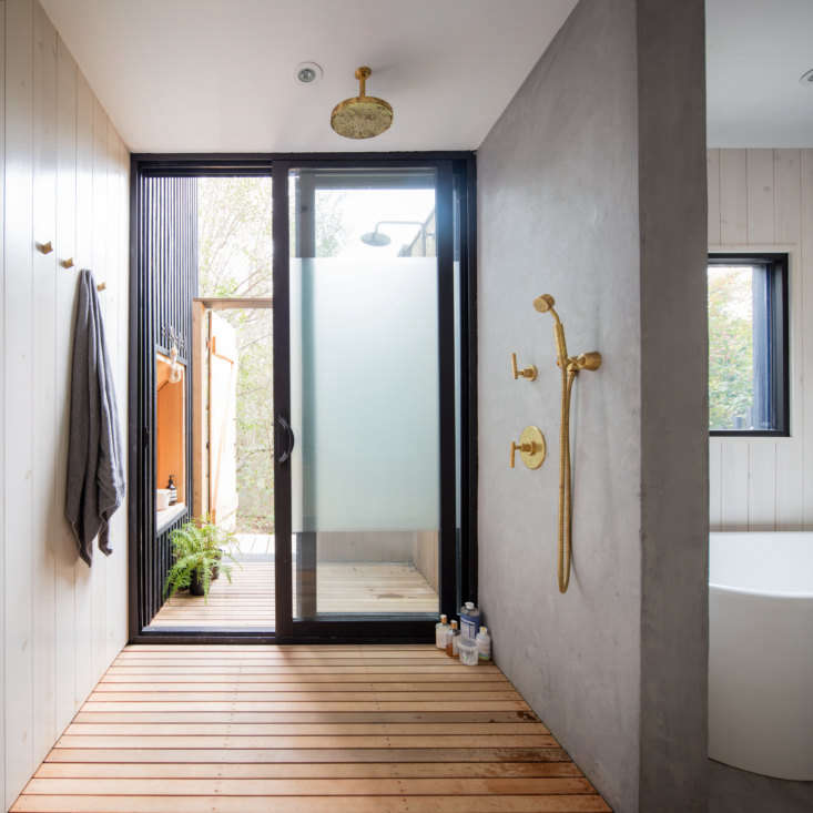 The ground-floor bath serves three bedrooms. It has both an indoor and outdoor shower, divided by an obscured-glass sliding door. The outdoor shower can be accessed from the side yard, so residents can have a post-beach rinse without coming indoors.