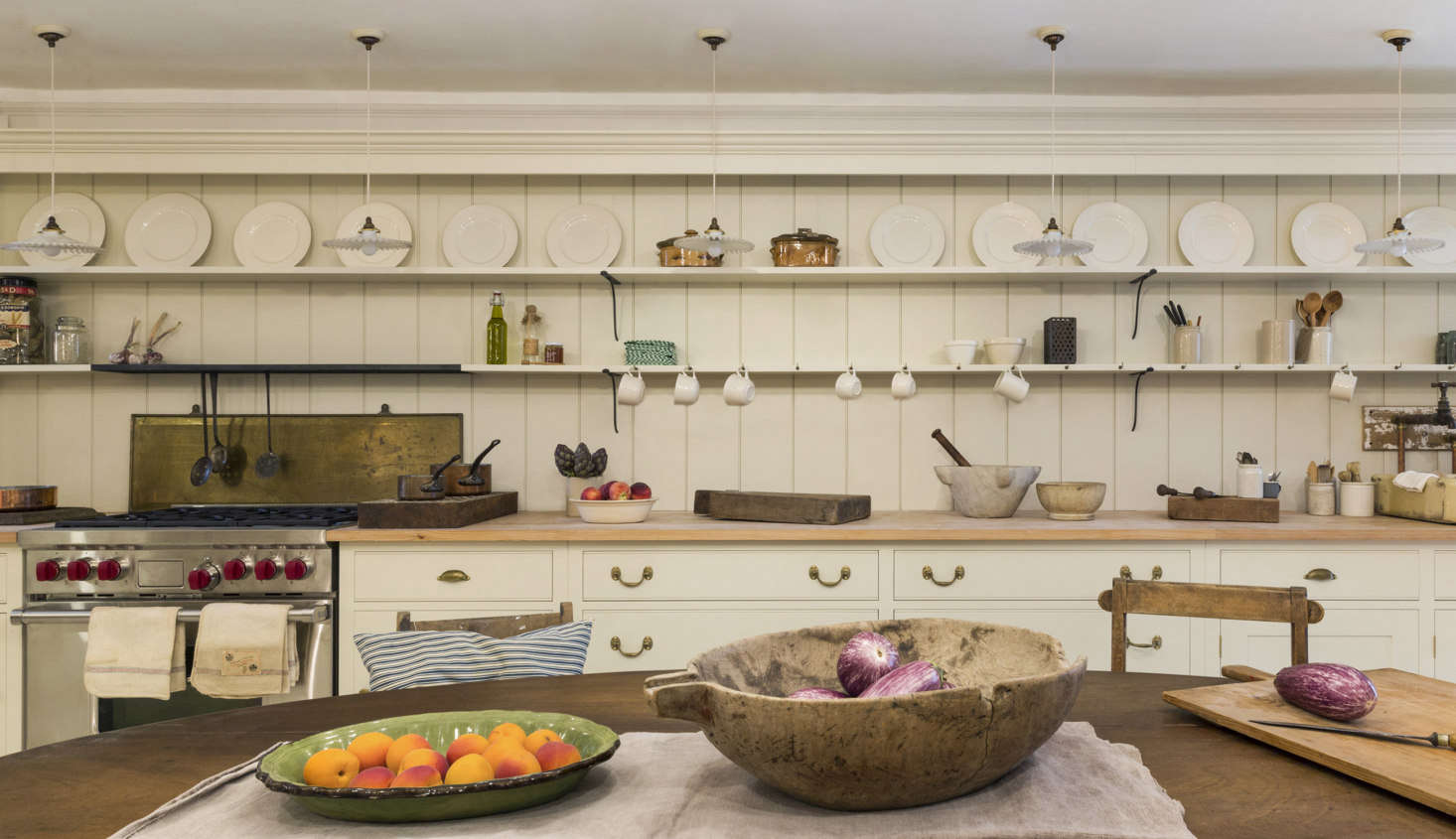 This is a working kitchen (in which just about everything happens to be for sale). It has a new Wolf range with an unusual backsplash made from a salvaged steel fireplace liner.