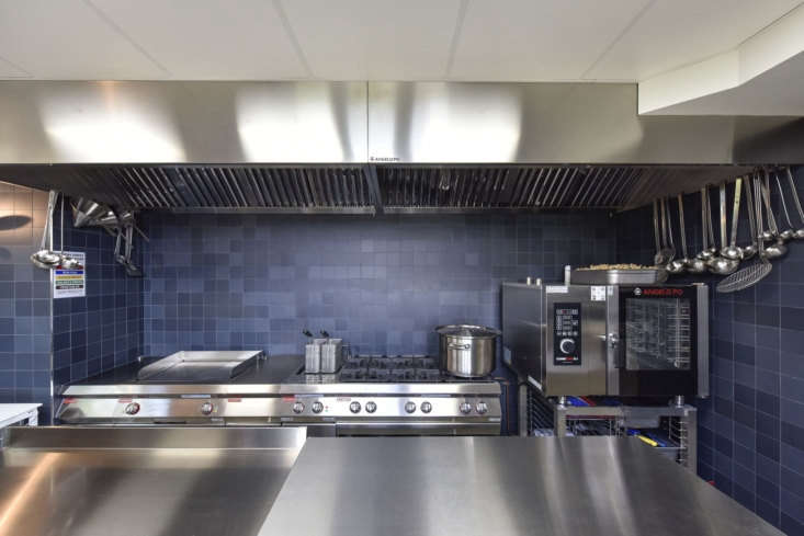 The stainless steel kitchen is clad in tonal blue tile.