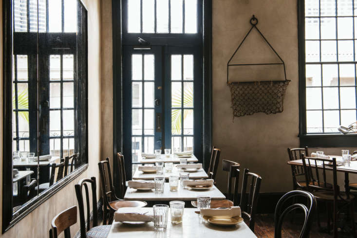 Seaworthy An 1832 Cottage Turned OldWorld Oyster Bar in New Orleans The second floor has high ceilings and stately windows trimmed in blue that step out onto the balcony. The chairs are a mix of Thonet and spindle back.