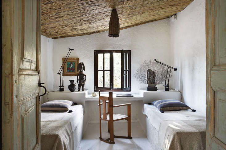 Spanish Eclectic An Airy Stable Turned Guest House on the Mediterranean Coast Beneath a sloped ceiling, twin beds are laid on built in stone platforms and a shelf behind serves as both desk and headboard.