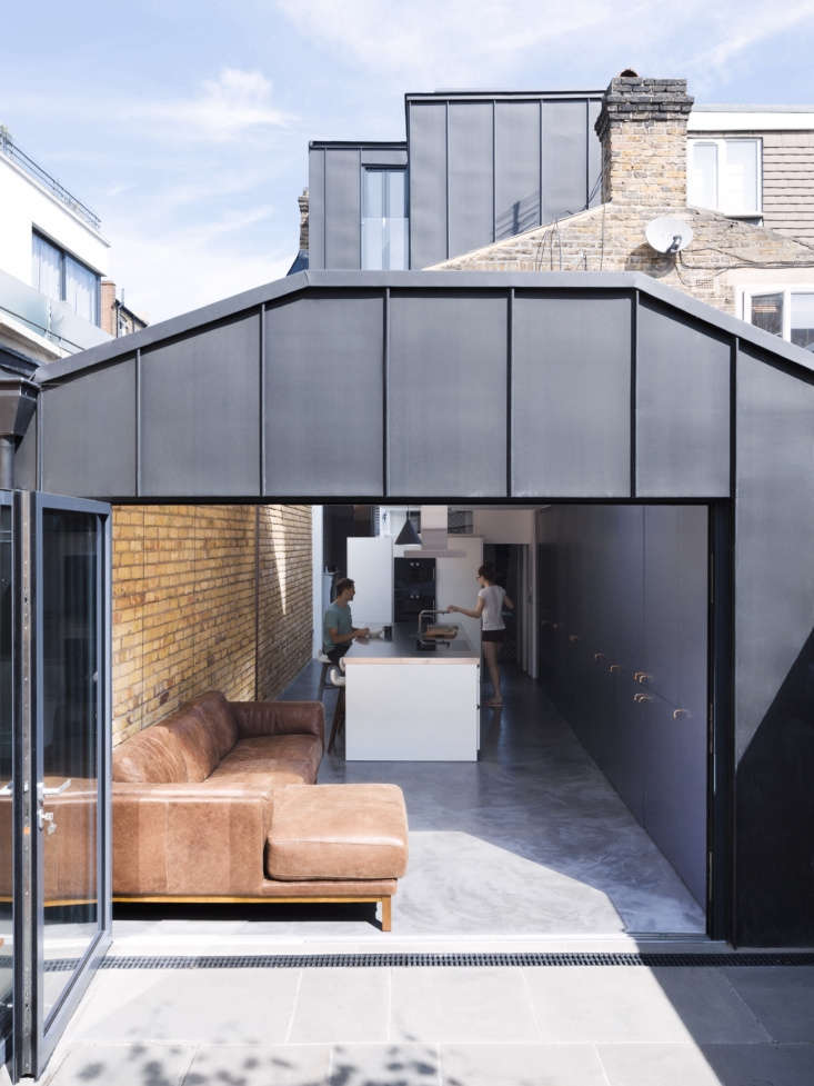 Under the Eaves A Brick House Reinvention in South London by Simon Astridge In the back of the house, in place of a small porch (scroll to the bottom for a Before shot), Astridge built a 350 square foot kitchen/sitting area extension with an accordion steel frame door that opens onto the terrace and garden.